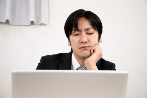 PCを眺めながら悩んでいる男の写真