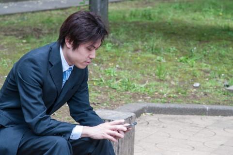 スマートフォンを外で操作している男の写真