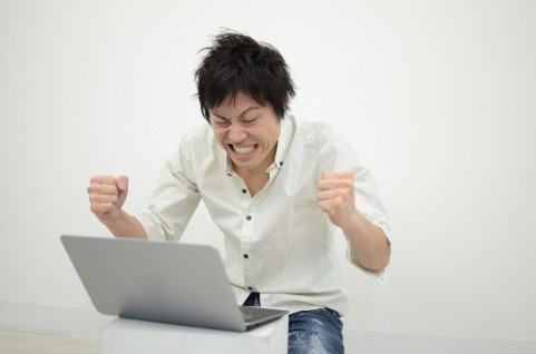 PCn画面を見て喜んでいる男の写真