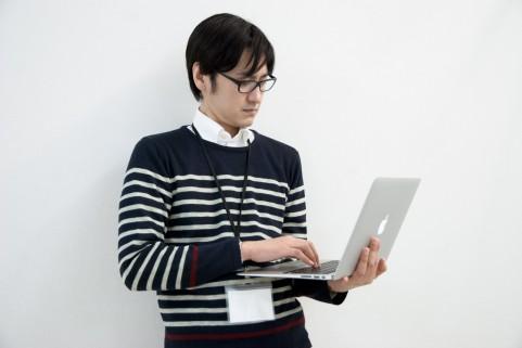 PC画面wを眺めていいるいる男の写真