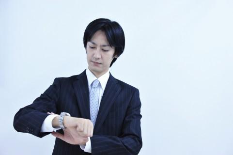 時計を気にしている男の写真