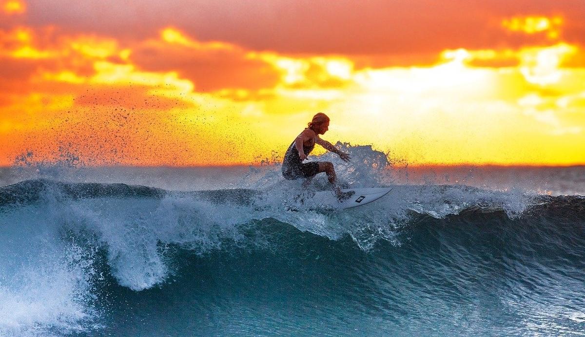 夕日を受けてサーフィンする人