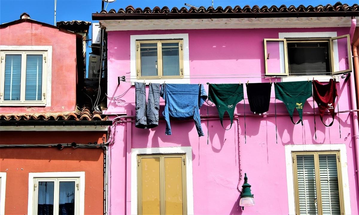ヴェネツィアのカラフルな家の前に洗濯物を干してある
