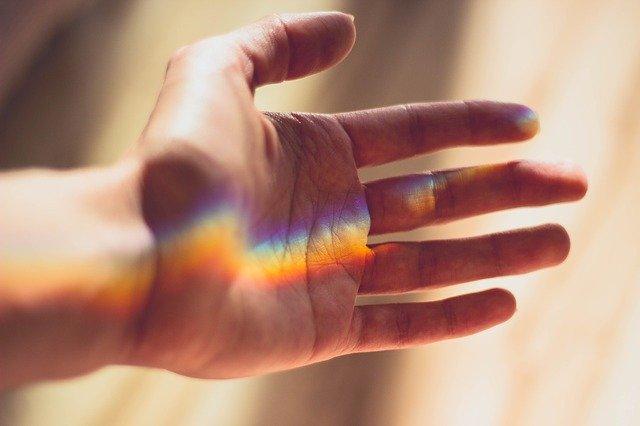 手に虹色の光が映っている
