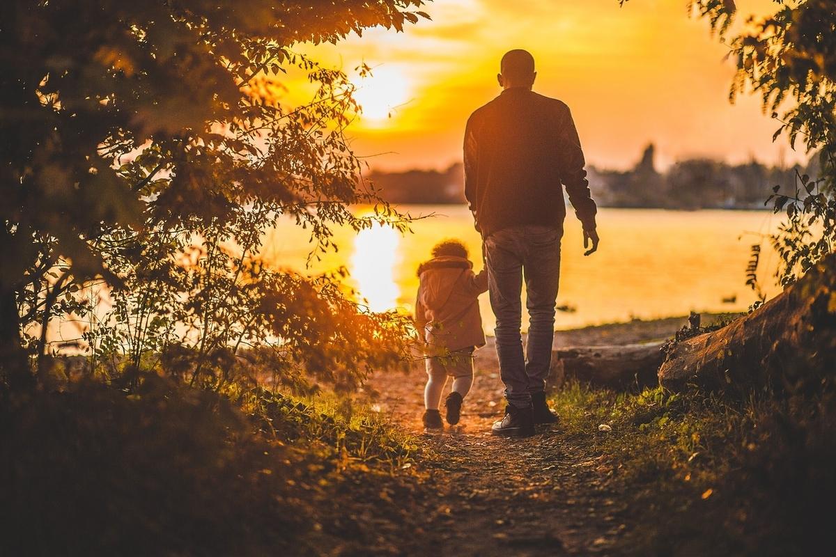夕日の中を歩く父と子