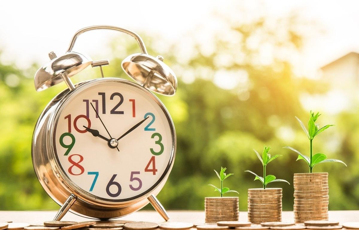 時計と積み上げられたコイン、投資するイメージ