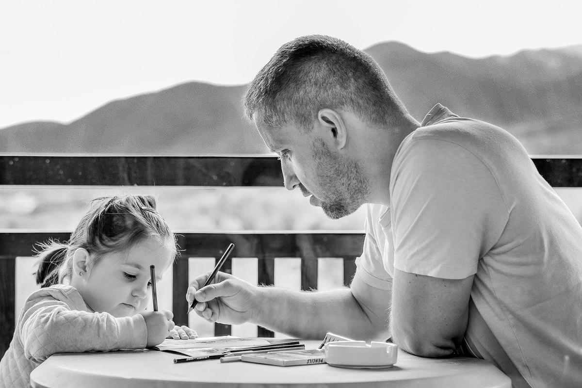 女の子と一緒に勉強しているお父さん