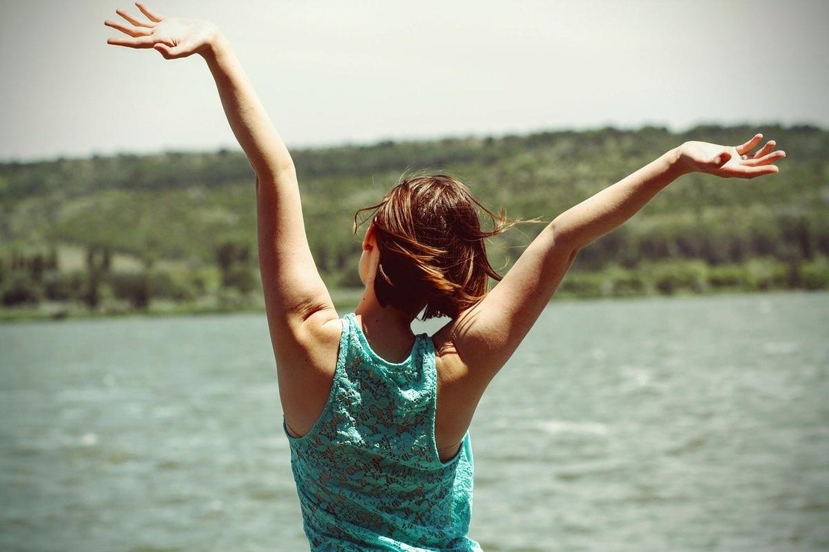 両手を挙げて解放感を味わう女性の後ろ姿