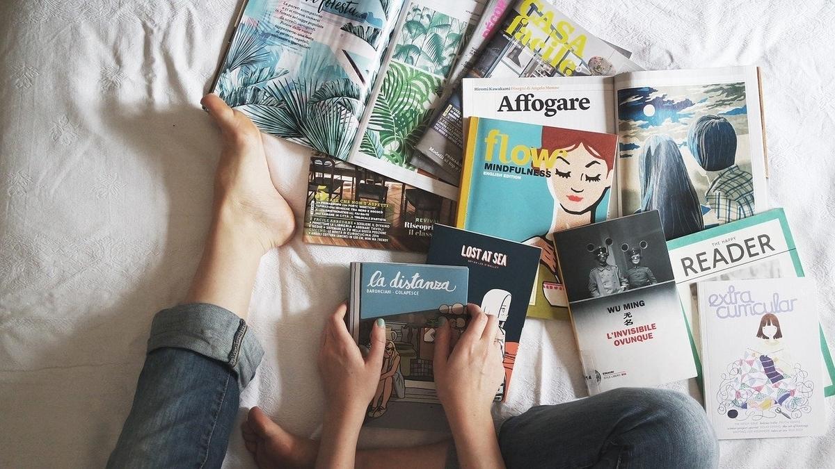 さまざまな雑誌を足下に広げている