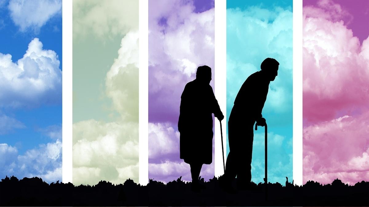 杖をついてぼんやりした風景の中を歩くお年寄り