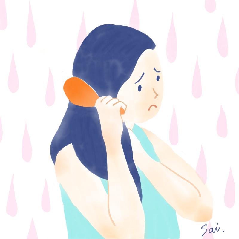 髪にブラシをあてる女性