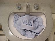 洗面台でワイシャツを洗う