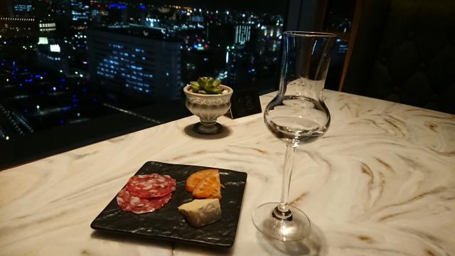 夜景の見えるバーとワイングラスの写真