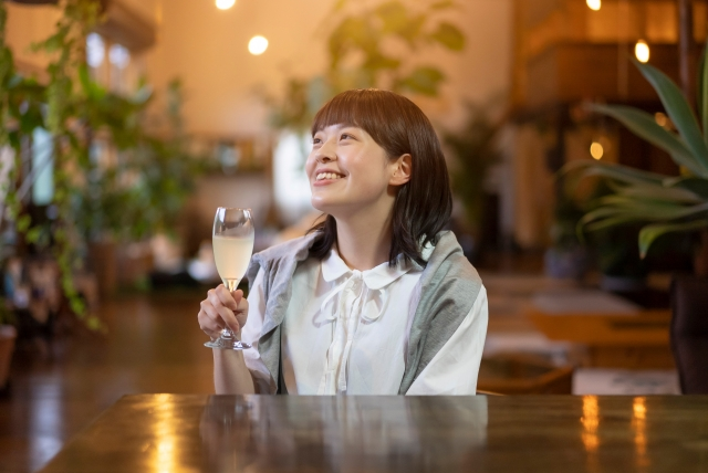 女子がワイングラスをも持っている画像