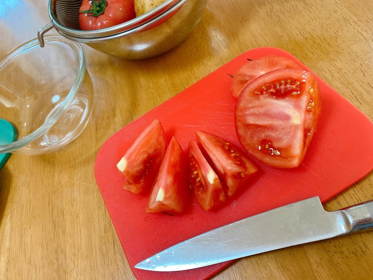 赤い小さなまな板の上でトマトを切る写真