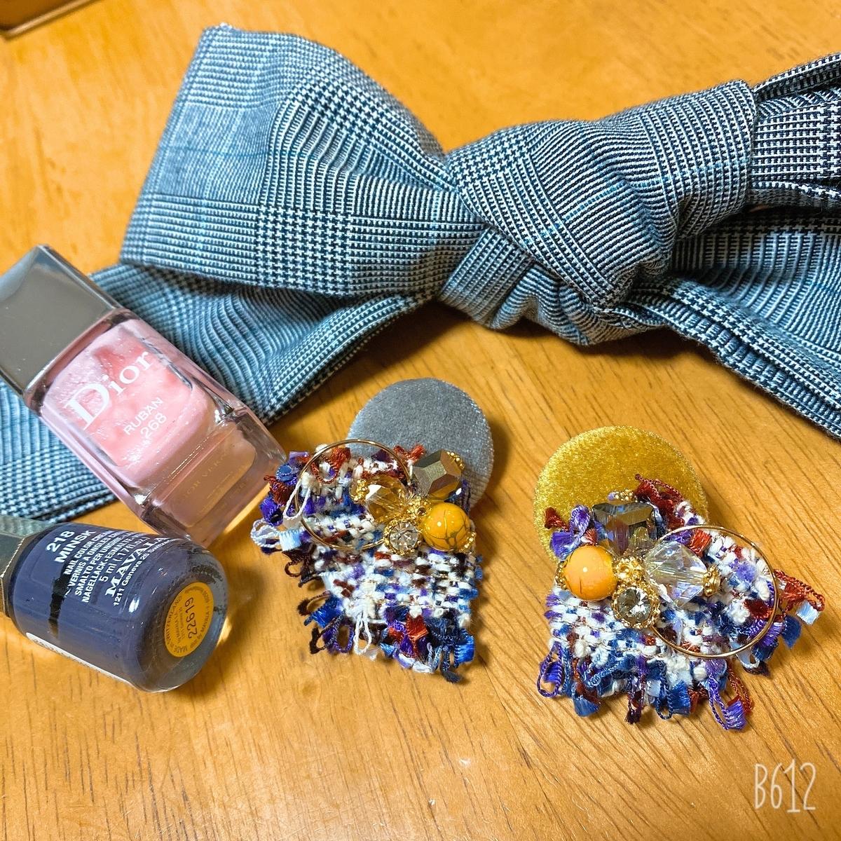 グレーとマスタード色のイヤリング・グレンチェックのリボン・ビンクとグレーのマニュキュアの写真