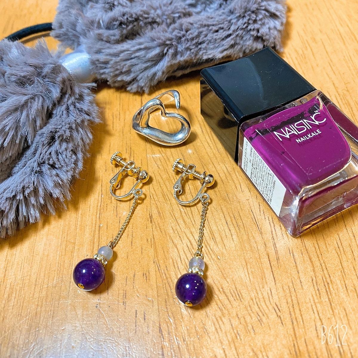 紫色のイヤリング・紫色のマニュキア・シルバーのリング・グレーのリボンの写真