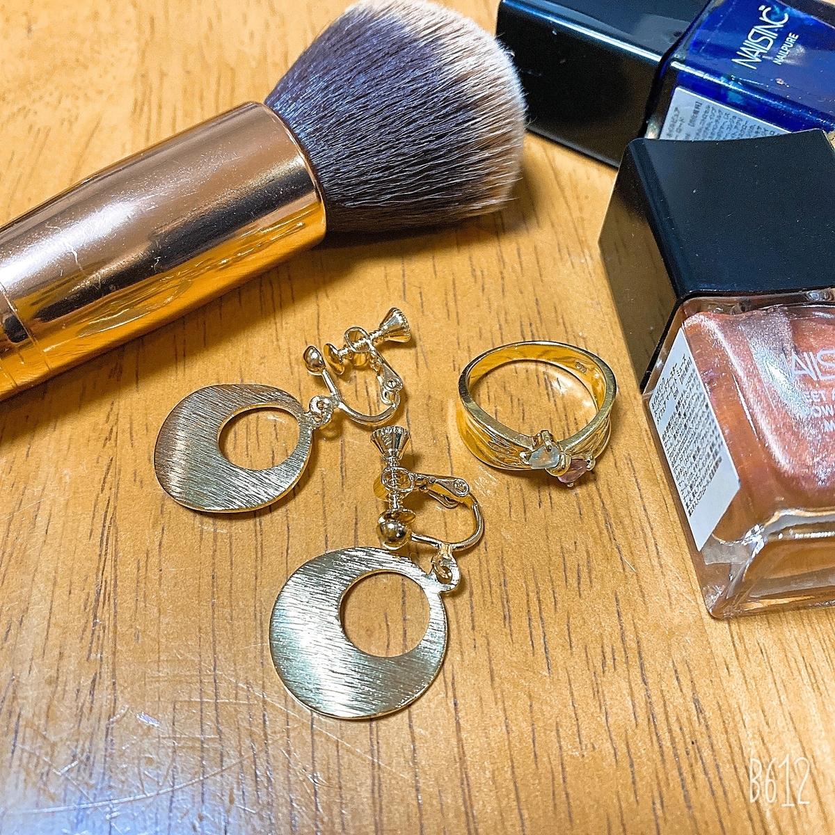 ゴールドのイヤリング・ピンクとブルーのマニュキア・ゴールドのリング・メイクブラシの写真