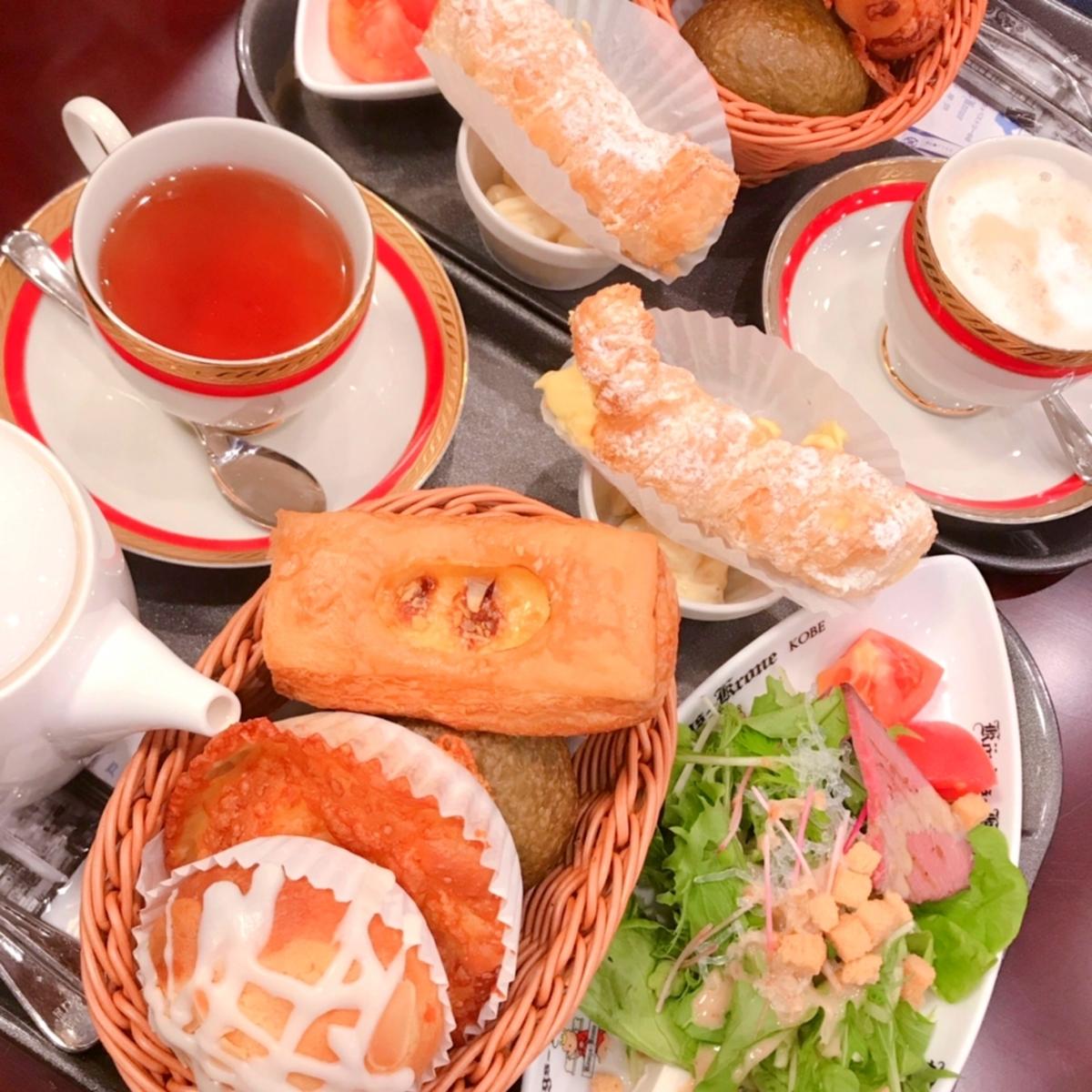 紅茶とグリーンサラダ、小さなパンがいくつか載った写真