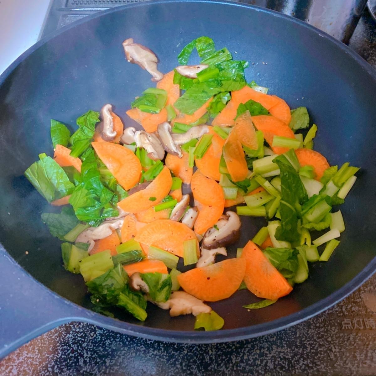 フライパンで野菜を炒めている写真