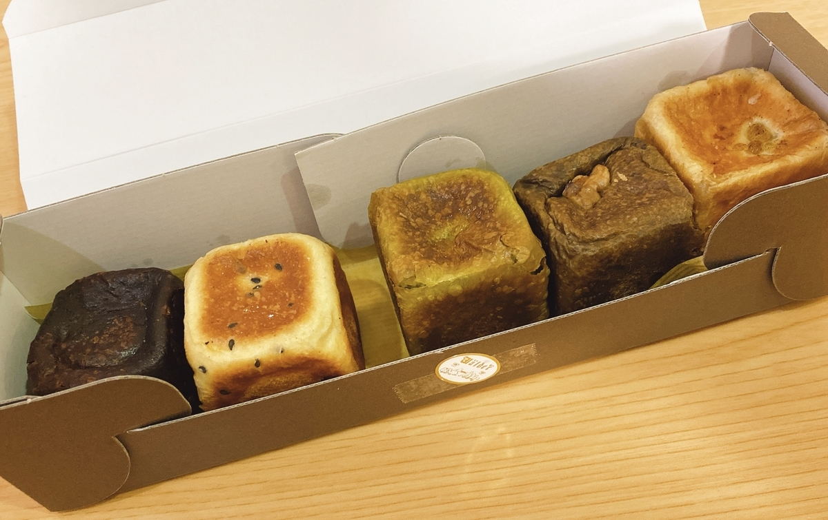 こげ茶の箱に入れられた5種類のあんぱんの写真