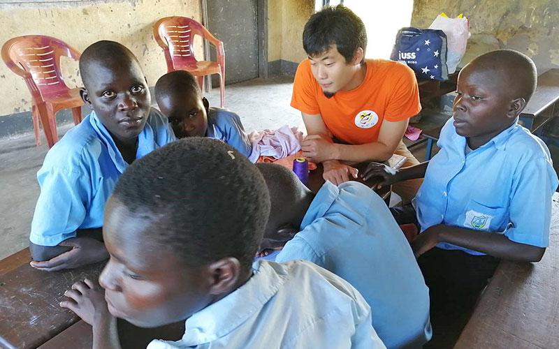 ウガンダ北東部の小学校で女子生徒らに布ナプキン製作の指導をする筆者