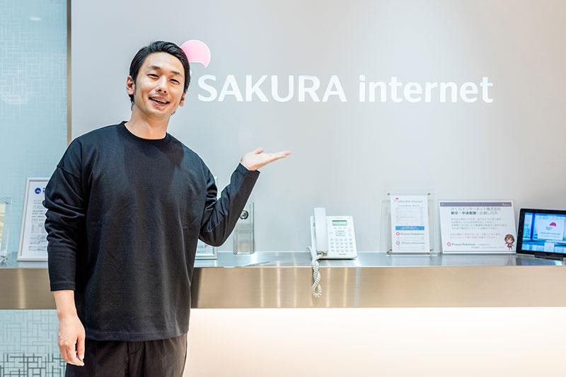 さくらインターネットのロゴ前で写真を撮る大川さん
