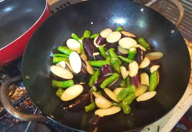 中華鍋でなすとししとうを炒めているところ