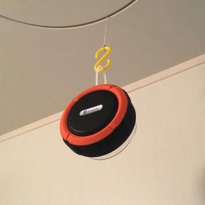 お風呂場に S字フックで吊るされた ブルートゥース スピーカー