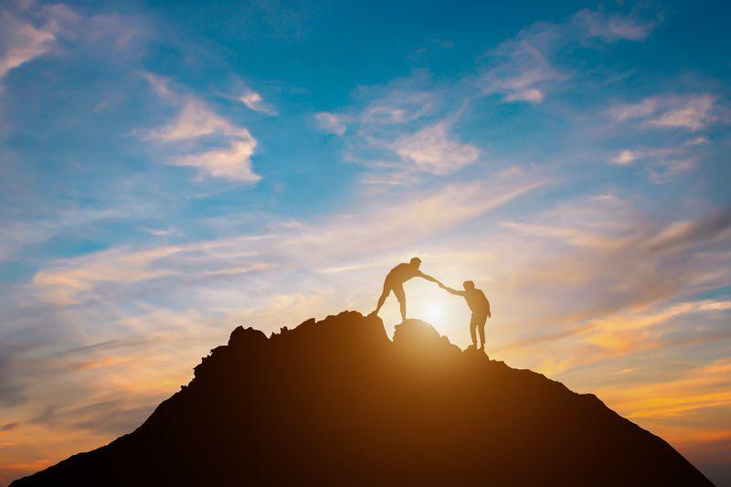 山を登ってくる人を登った人が手助けする様子