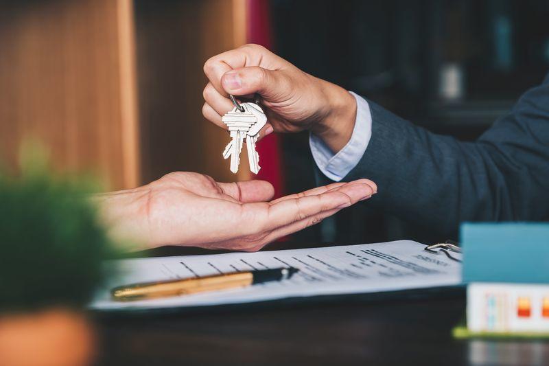 家の鍵を渡す人。売る行為を表した写真