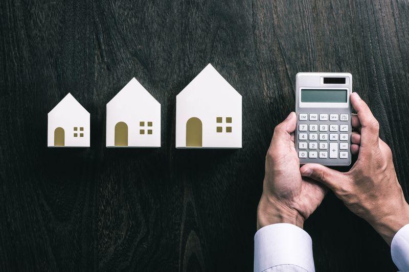 家の模型3つとその横で電卓を触る人の手