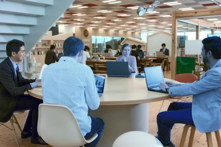 テーブルにいる4人のうち、3人はインターネット上で参加している。5Gによって、その場にいない相手とも、距離を感じないコミュニケーションが可能