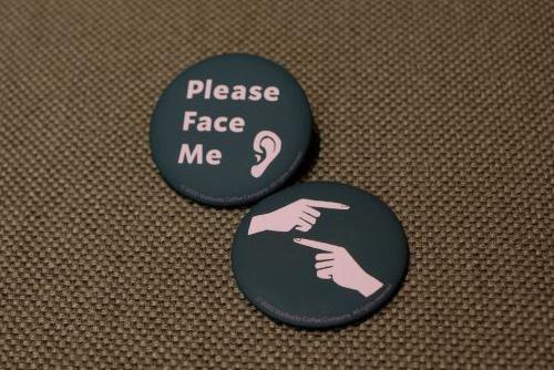 「Please Face Me(こちらを向いてください)」と「耳」が描かれたバッジは聴覚障がいのあるパートナーが、「手」が描かれたバッジは「手話ができます」という意味で、聴者のパートナーがつける。