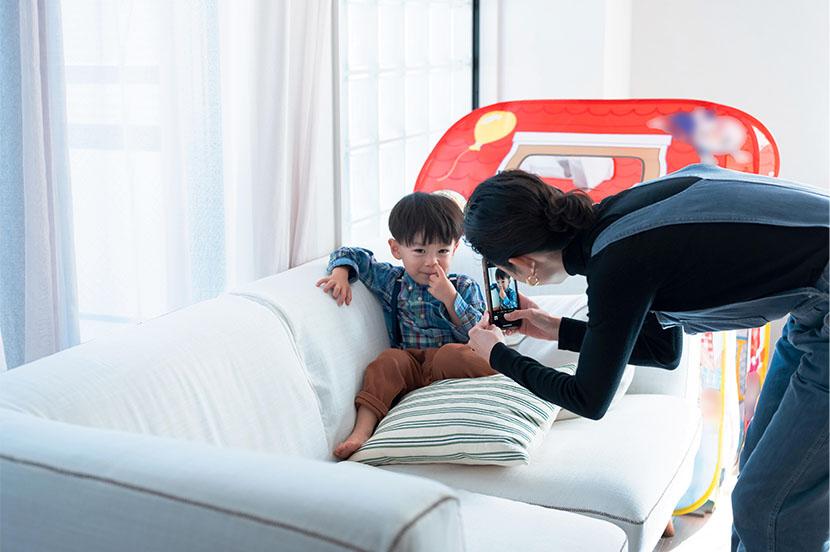 ソファの上に座る正太郎くん。お母様が、名前を呼んだり「いないないばあ」をしたりしながら、興味を引きつけて……パシャリ!