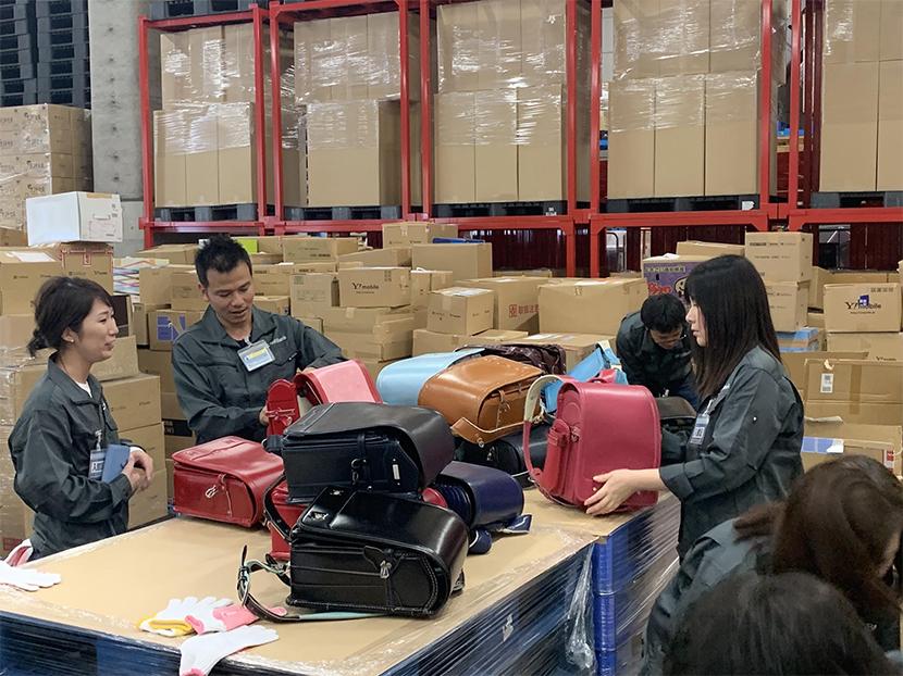 集まったランドセル梱包作業の様子 | 「愛のランドセル」寄付プロジェクト