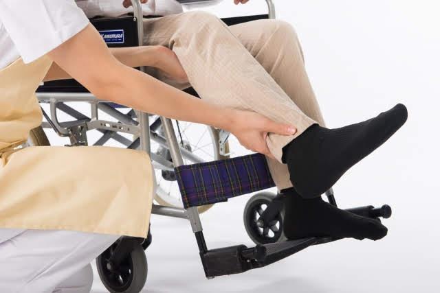 車いすに乗った老人の脚を持って介護士が介助している画像
