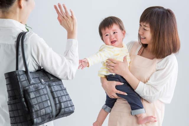 仕事へ向かう母親が子供を保育士にあずけ、手を振りながら我が子にバイバイをしている画像