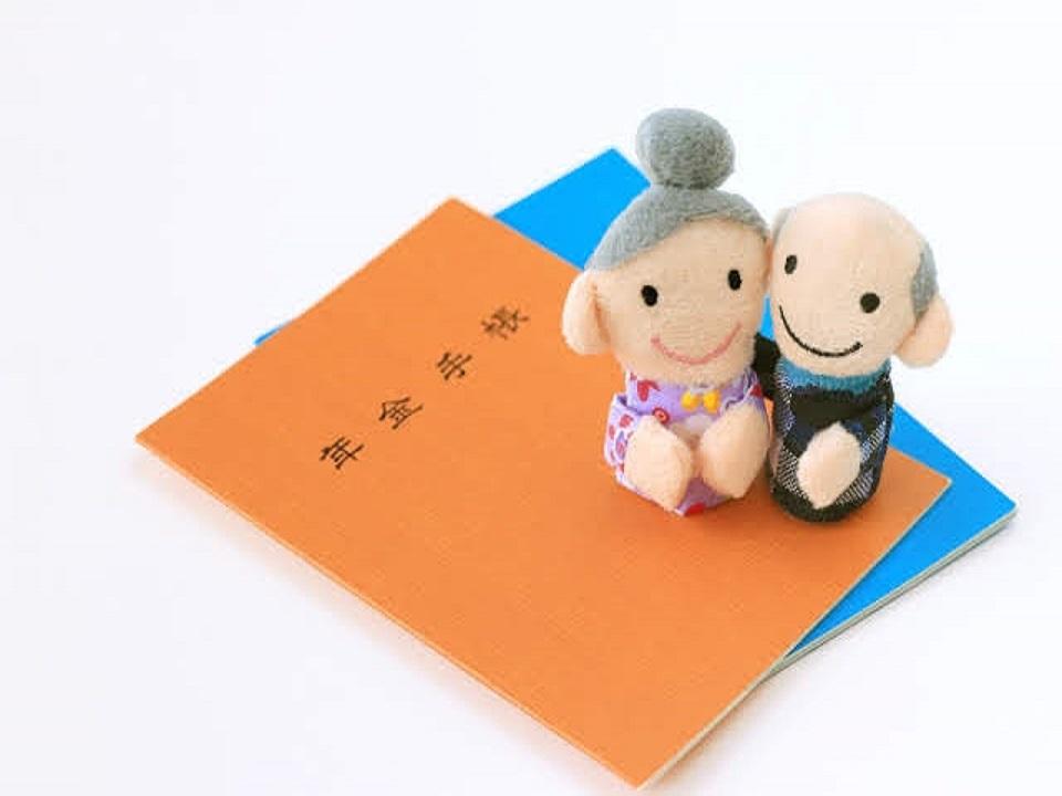 年金手帳とおじいさんとおばあさんの人形の画像