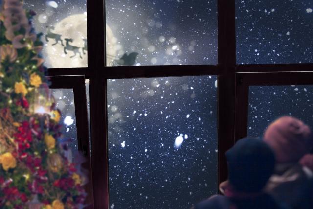 空飛ぶそりに乗ったサンタクロースを窓から眺めている画像