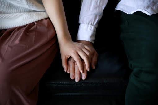 男性の手の上に自分の手をのせている女性の画像
