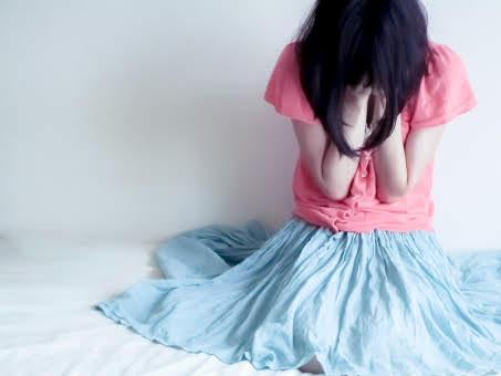 座り込んで顔を抑えて泣いている女性の画像