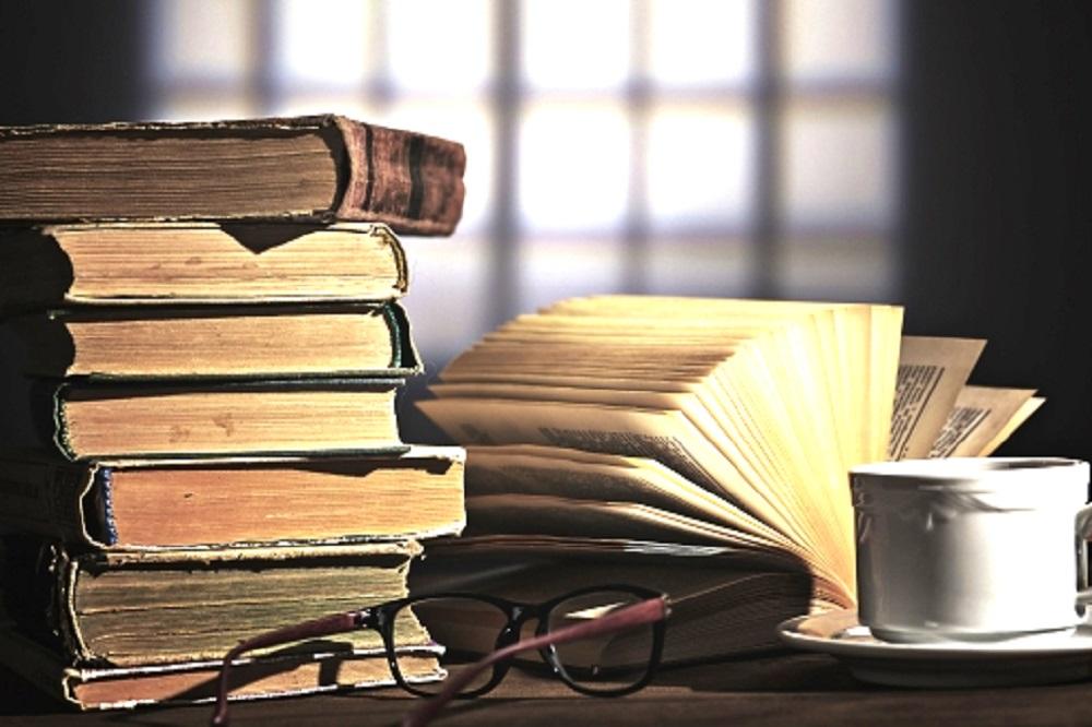 机の上の古い本とコーヒーとメガネの画像