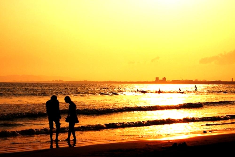 波打ち際で夕景を眺めているカップルの画像