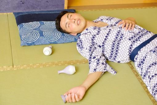 酔っ払って寝てしまっている男性の画像