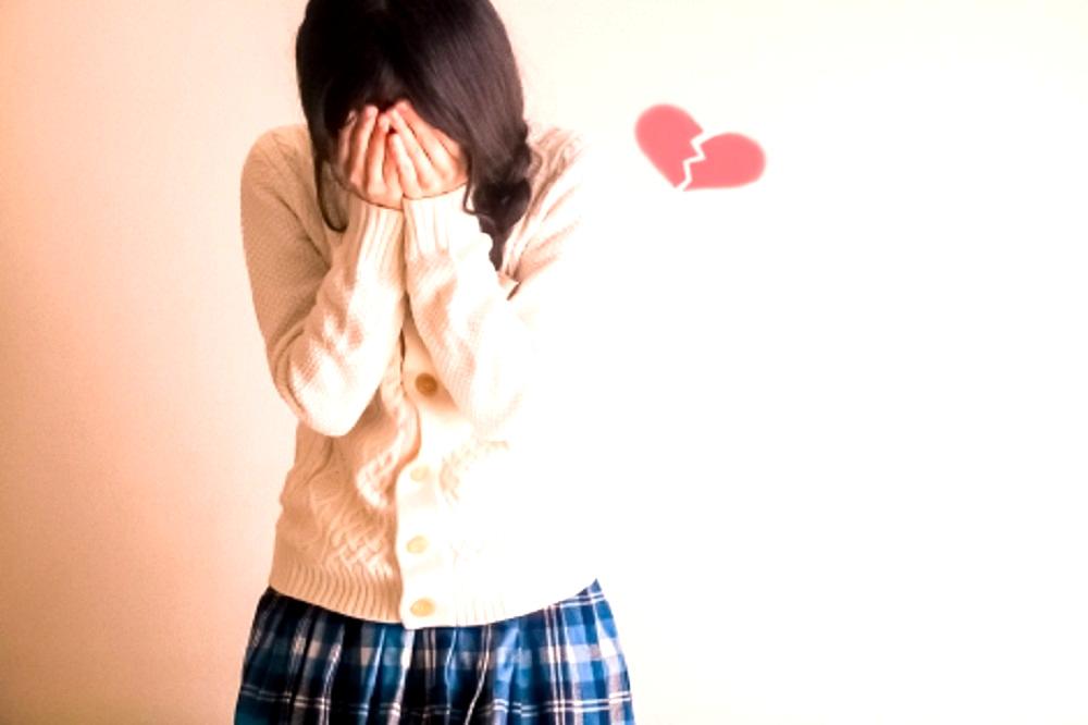 割れたハートの横で顔を手で覆って泣いている若い女性の画像