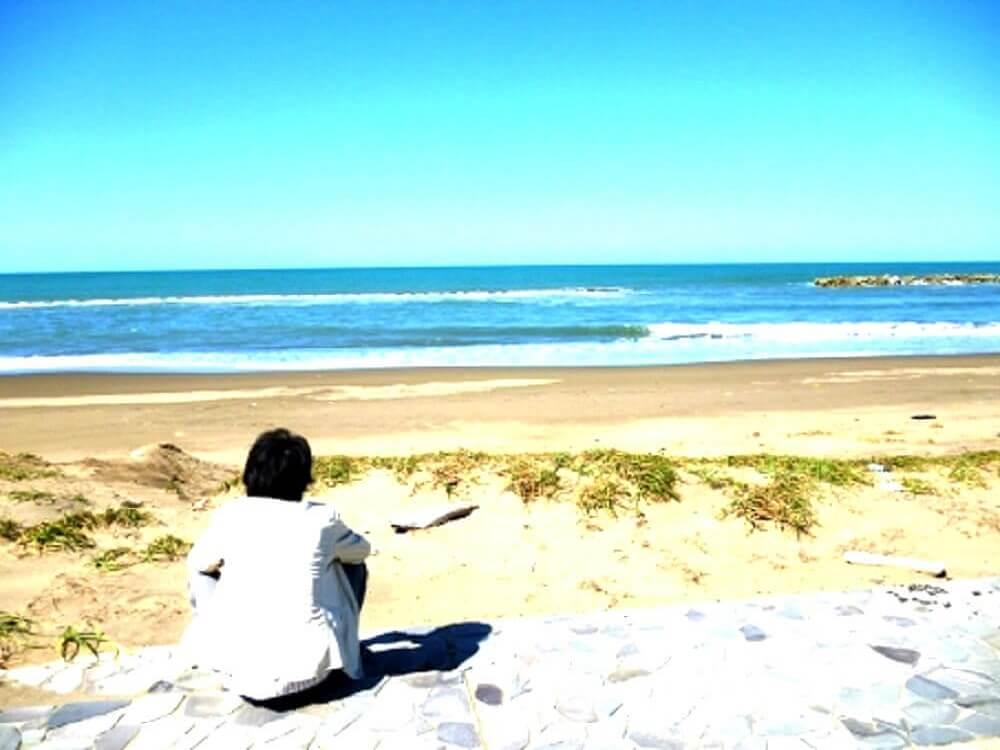 砂浜で海を見ながら黄昏れている男性