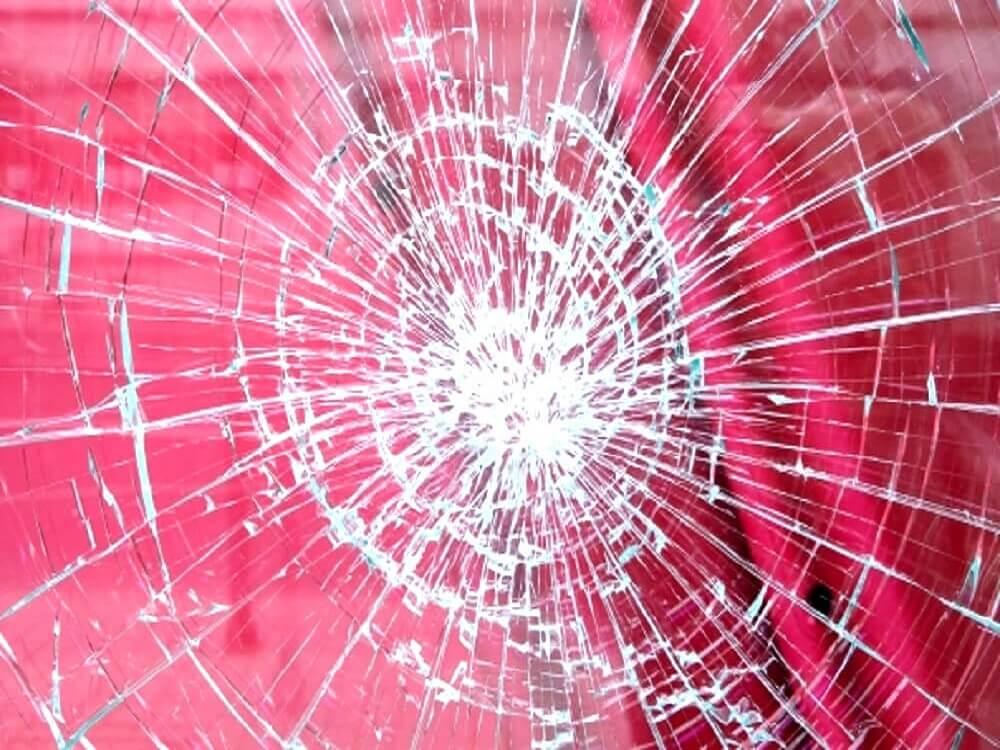 赤い背景の前のガラスがひび割れている