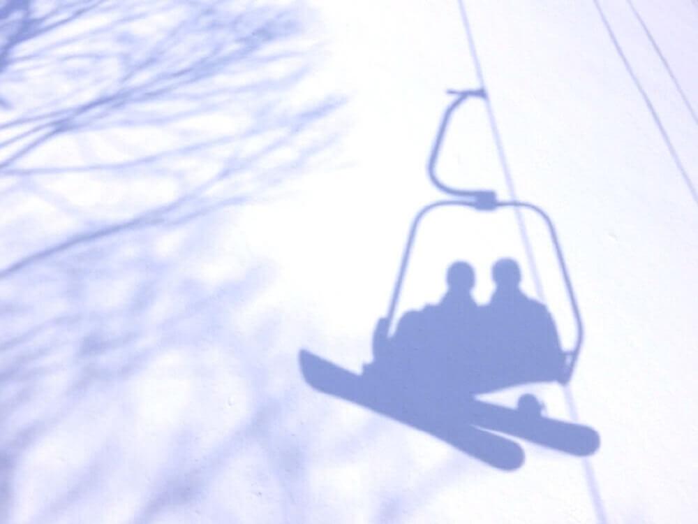 スキー場でリフトに乗っている二人の影がゲレンデに写っている画像