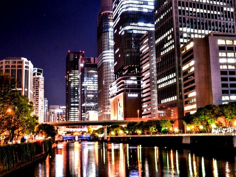 大阪市内の河川のバックにそびえるオフィスビル群の画像